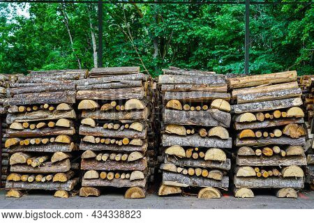 Firewood Stack, Mostly Made Of Halved Tree Trunks, Neatly Stacked Alternately Lengthways And Crosswa