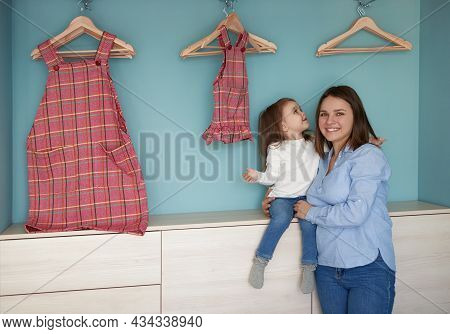 Happy Young Mom Hugging Cute Toddler Girl Near Wardrobe With Similar Dresses Hanging On Hangers