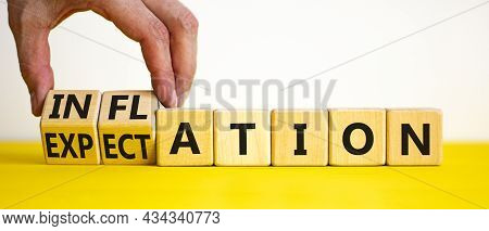 Inflation And Expectation Symbol. Businessman Turns Cubes, Changes The Word Inflation To Expectation