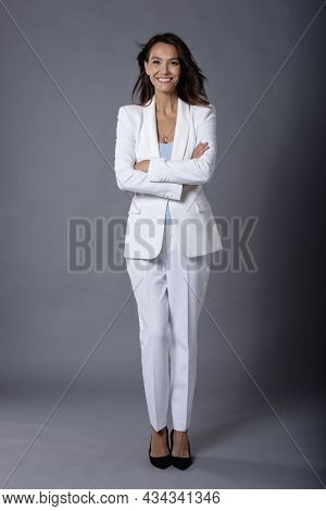 Full Length Studio Shot Of Attractive Middle Aged Woman With Toothy Smile Wearing Suit While Standin