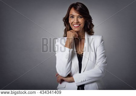 Studio Portrait Shot Of Attractive Middle Aged Woman With Toothy Smile Wearing Blazer While Standing