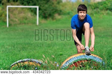 teenage boy exercising outdoors, sports ground in the yard, he ties his shoelaces and does a warm-up, healthy lifestyle