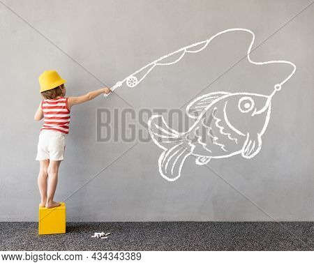 Dream Big! Happy Kid Draws A Chalk Fish On The Wall. Children Imagination And Summer Vacation Concep