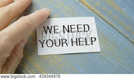 Businesswoman Holding A Card With Text We Need Your Help. Business Concept