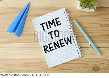 Notepad With The Text Time To Renew On A Wooden Background, Near Glasses And Stationery.