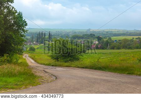 Rural Landscape. Country Road In A Village With Houses And Vegetable Gardens On A Summer Day.