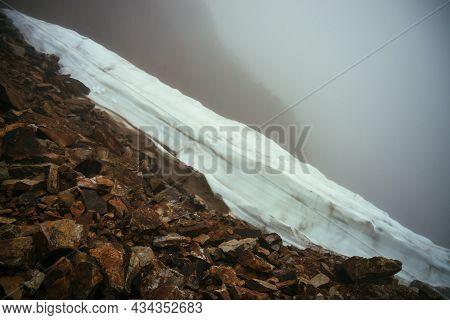 Gloomy Minimalist Foggy Mountain Landscape With Snow Cornice Over Abyss Inside Cloud. Above Snow Cor