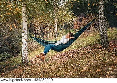 Young Woman Enjoying Warm Autumn Weather And Relaxing In Swinging Hammock Between The Birch Trees. O