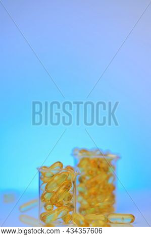 Fish Oil Capsules In Glass Laboratory Flasks On A Blue Background.omega 3 Capsules. Supplements And