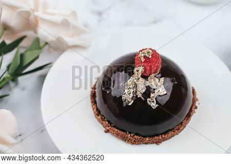 Chocolate Mousse Cake With Berries With Rose Flower On Marble Table. Delicious Homemade Cake.