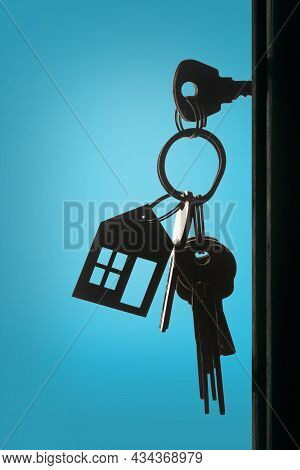 Silhouette Of The Keys With Keyring In The Door Keyhole With Blue Background