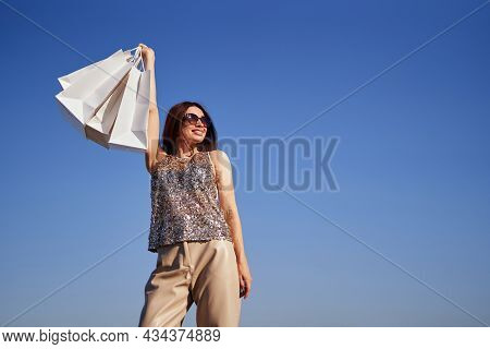 Attractive Shopaholic Brunette Girl Rejoices In Shopping Against The Blue Sky Holding Shopping Bags