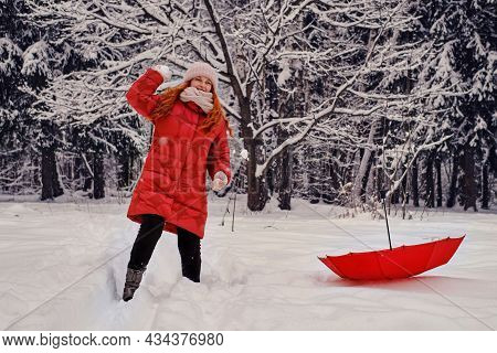 A Happy Woman Is Playing Snowballs In A Winter Forest With Trees In The Snow