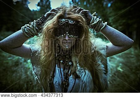 A frightening forest witch with a mask covering her eyes stands in a gloomy forest. Woman shaman. Paganism. Death ritual. Halloween.
