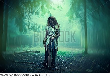 Woman shaman. Full length portrait of a frightening forest witch with a mask covering her eyes standing in the magic forest at night. Paganism. Death ritual. Halloween.