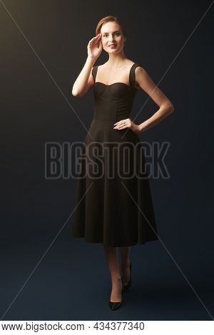 Beauty and makeup. Full length portrait of a slender young woman wearing a black tight-fitting dress in a black background. Evening fashion. Studio portrait.