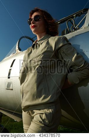 Confident smiling woman pilot with bright red lips and black sunglasses in pilot uniform poses next to the fighter jet.