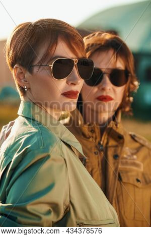 Two beautiful professional female commercial aviation pilots in stylish uniform and sunglasses with bright red lips posing at the airport. Aviation.
