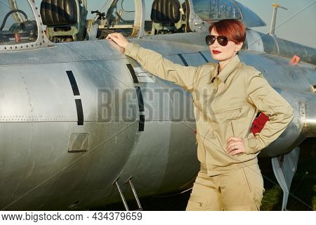 Commercial aviation. Professional confident female pilot in uniform and sunglasses posing by her fighter-jet ready to start the flight any moment.