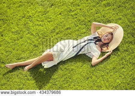 Portrait of a romantic blonde girl in an elegant white dress and wide-brimmed straw hat lying on a green lawn. Summer vacation. Summer beauty, fashion.