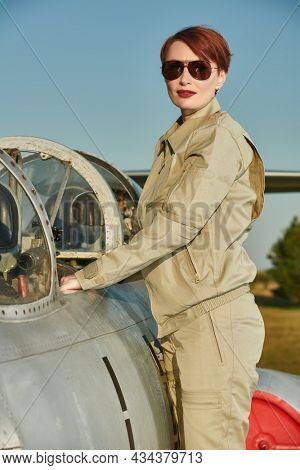 Professional commercial pilot woman wearing a uniform and sunglasses posing at the aircraft cockpit before taking off. Aviation.