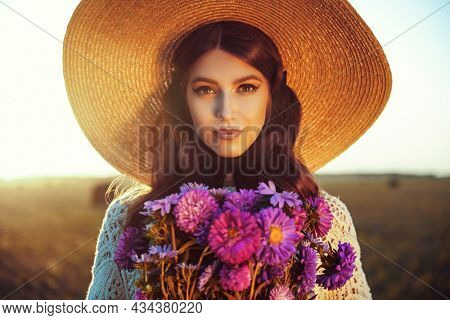 Autumn beauty girl. Portrait of a beautiful romantic girl in elegant wide-brimmed hat holding a bouquet of flowers in the background of a hayfield. Makeup and cosmetics.