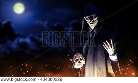 Portrait of a dangerous person with skull makeup dressed in a black robe with a hood holding a human skull in his hands surrounded by fire. Dark moonlit night background with copy space. Halloween.