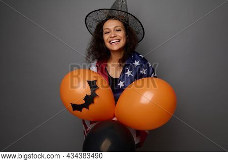 Attractive Young Woman In Wizard Hat, Wrapped In American Flag, Holds Colorful Orange Air Balls, Smi