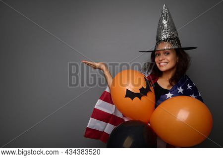 Attractive Woman In Wizard Hat, Wrapped In American Flag, Holds Orange Air Balls, Smiles Toothy Smil