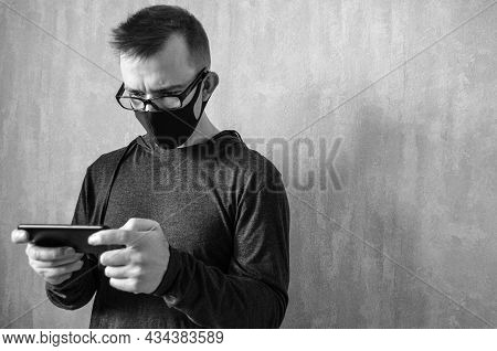 Caucasian Man With Glasses In Protective Mask On Gray Background With Copy Space. Monochrome Portrai