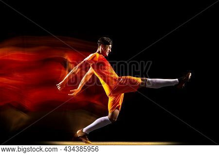 Portrait Of Young Sportsman, Soccer Football Player Training Isolated Over Black Background In Mixed
