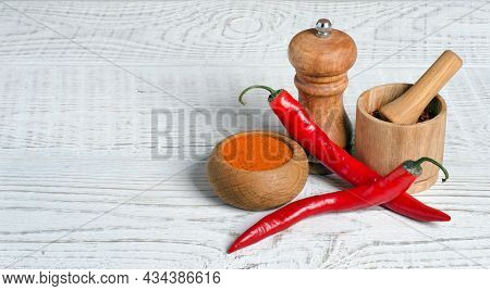 Chili Pepper Pods And Red Ground Pepper In Bowl On White Wooden Background With Copy Space For Your