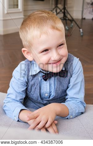 Vertical Portrait Of A Five-year-old Blonde Boy In A Shirt, Vest And Bow Tie