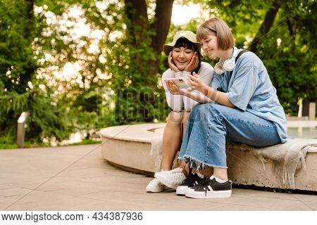 Multiracial two women using cellphone and laughing while resting in green park