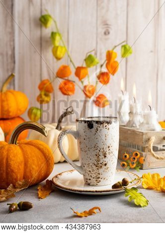 Autumn still life with cup of tea, pumpkins,flowers and candles on table.Thanksgiving day or halloween concept.