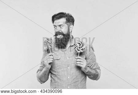Crazy Hungry Hipster Look At Rainbow Spiral Colourful Lollipop Candy On Sticks Sticking Out Tongue Y