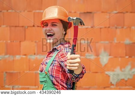 Cheerful Kid In Helmet Hold Hammer. Carpentry And Woodworking Concept. Teen Child Using Hammer Tool.
