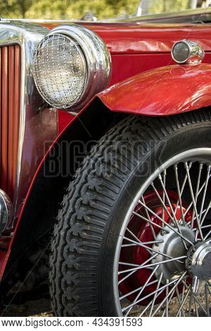 Partial View Of A Red Vintage Car With Spoke Wheel And Front Light