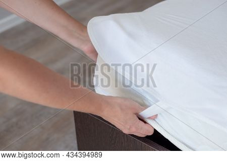 The Woman Makes The Bed, Putting On A Protective Waterproof Cover On The Mattress. Clean Linen And C
