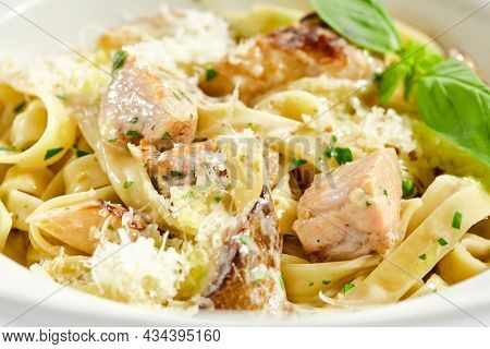 Traditional Italian lunch - pasta fettuccine with chicken and mushrooms with parmesan cheese. Creamy pasta with mushroom and chicken. Chicken and mushroom in cream sauce with homemade pasta