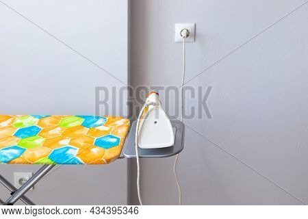 Electric Iron Plugged Into An Outlet On An Ironing Board Against A Gray Wall. Ironing Clothes.