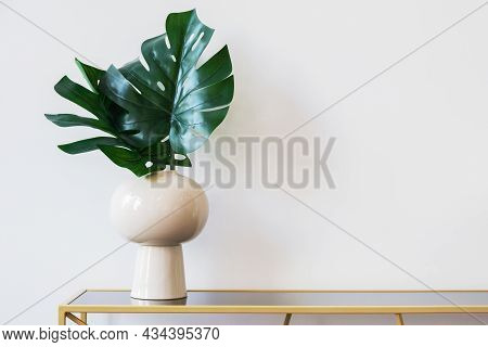 Minimalistic Image Of A Vase With Monstera Leaves Against A White Wall