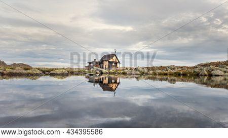 Small Alpine Hut Mirrored In Mountain Lake