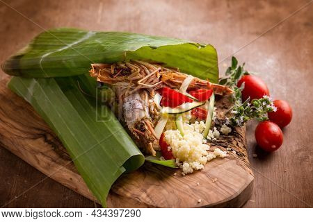 shrimp coucous with zucchinis cooked on banana leaf