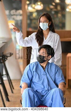 Doctor Or Caregiver With Disabled Male Patient In Wheelchair