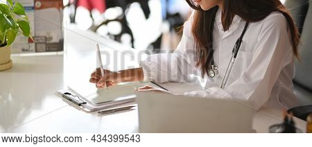 Young Female Intern Doctor Learning A Medical Case On Digital Tablet