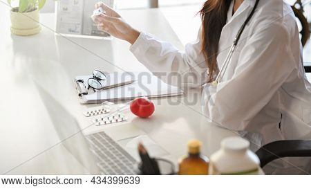 Side View Of Asian Female Doctor Working On Her Desk