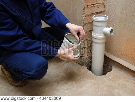 Plumber assemble gray pvc sewage pipes.