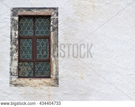 Old Leaded Glass Transom Window With Stone Surround And A Light Colored, Textured Plastered House Wa