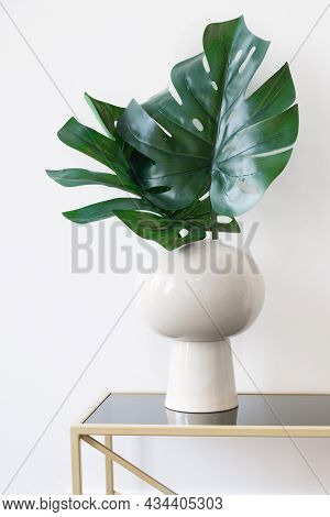 Vertical Minimalistic Image Of A Vase With Monstera Leaves Against A White Wall